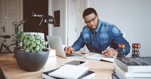 home office work. Shot Of Afro American Young Man In A Home Office Using Laptop And Taking Notes. Work