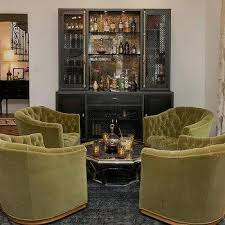 hollywood regency green and black living room with industrial metal casement bar cabinet