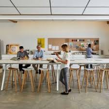 creative office space large. Group Of People Around A Large Conference Table With Wooden Bar Stool  Seating And Woman Creative Office Space