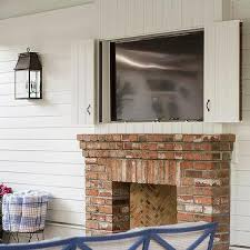 covered patio with concealed tv over fireplace