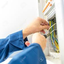 electrician installing an electrical fuse box in a house working electrician installing an electrical fuse box in a house working pliers on the wiring circuits