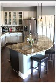 The unique curved kitchen island provides extra casual seating in the  kitchen and also gives the large kitchen extra counter space, making meal  pre
