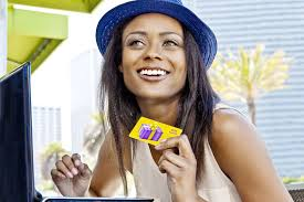 woman holding a gift card and using a laptop