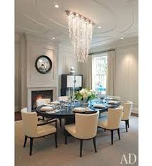 formerly a deep claret the dining room was reved with a fireplace light gray walls and ceiling details that frame the chandelier and echo the custom