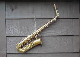 alto saxophone hanging on garden shed brown gold