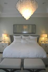white bedding and white pillows also bedside table