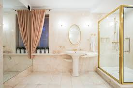 fancy shower with glass door and golden frame