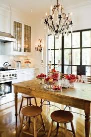 rustic wooden dining table with red fruit on table and chandelier in contemporary kitchen image