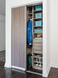 a brown melamine sliding door opens to a condo foyer closet filled with modular brown melamine shelving units and drawers next to a clothes rails
