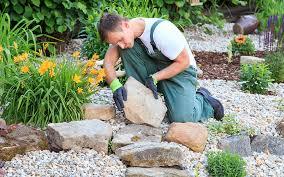 a man setting large stones into a landscape