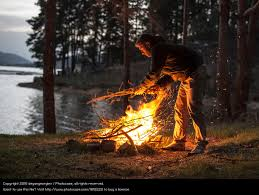 man lights a fire in the fireplace in nature at night a royalty free stock photo from photocase