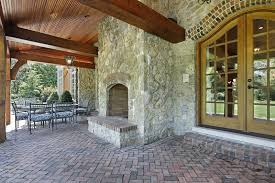 beautiful covered patio with red brick pavers and rustic outdoor stone fireplace