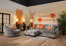The application of orange and cool grey in this living room set compliments  the contemporary aesthetic