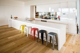 simple and easy a white modern kitchen with long kitchen island and sink plus small stools with simple design of white kitchen cabinets and cupboards on