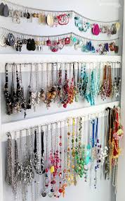 earrings and necklaces hanging on wall hooks