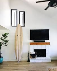 white brick fireplace with natural wood mantle california coastal open living room white fireplace wall surfboard californiacoastal fireplace