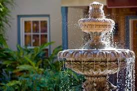 a garden fountain in the front of a residence
