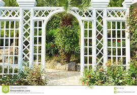 white wood gate in flower garden