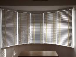 Wood venetian blinds in chalk colour fitted to a 5-sectioned bay window by  The