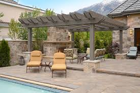 pergola and patio ideas in the backyard of stone house completed with outdoor stone fireplace and padded patio chairs plus table and lounge patio chairs