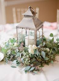 picture of a whitewashed candle lantern on a eucalyptus and white roses pad for a vintage or garden wedding tablescape