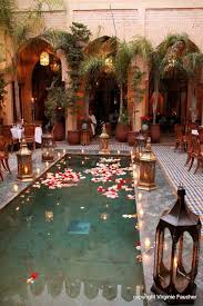 Marrakech pool adorned with customary wedding decor of brass lanterns,  luminous candles, and floating