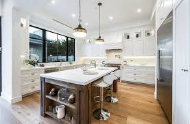 traditional kitchen with carrara marble countertops white cabinets and wood floors