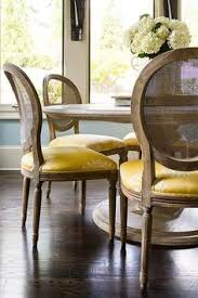 chic dining room features a round marble top dining table table lined with round cane back dining chairs accented with yellow seat cushions atop dark oak