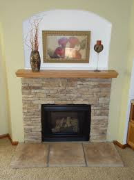 awesome stacked stone fireplace makeover with cream wall paint color and black place set and wall