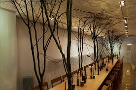 dinner at an art  on wall art with real tree branches with lively real tree table birds add mystery to dinner party