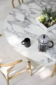 white marble table top. round marble dining table with timber chairs. white top