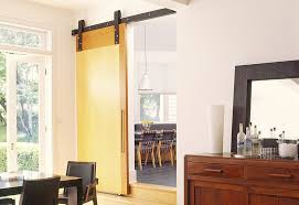 light filled modern dining room with a narrow entry and sliding barn door design