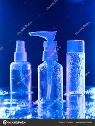 Blue Light Spray Three Spray Bottle Under A Blue Light Against Deep Blue