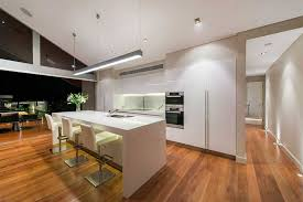 kitchen hanging fluorescent light fixture over white kitchen island with 3 barstools and kitchen sink