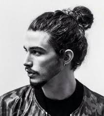 a photograph of a male model with the perfect man bun hairstyle for his long wavy