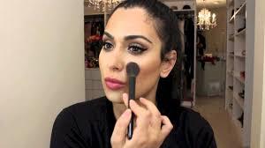 huda kattan brushing on makeup on her face