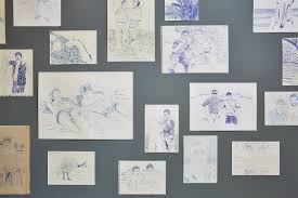 series of unframed sketches placed on grey wall