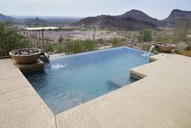 Infinity pool with small fountains overlooking desert landscape and hills.
