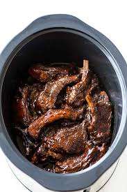 slow cooker full of tender pork ribs slathered with bbq sauce
