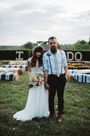 picture of a casual groom s look with a blue shirt thin leather suspenders black pants and brown shoes plus a creamy tie
