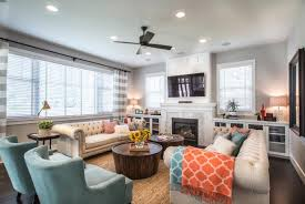 living room with cream tufted sofas turquoise armchairs circular wood coffee tables