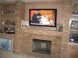 rustic exposed brick fireplace mantle with wall mount tv and natural ash wooden mantle shelf