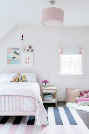 pink metal bed with pink and black striped rug
