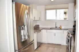walk into a chic kitchen with stainless steel appliances subway style backsplash quartz countertops with an undermount sink and white shaker cabinets