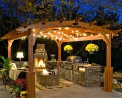 chic outdoor kitchen designs with wooden pergola using stunning string lights and stone cabinet plan