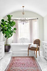 bathrooms white bathroom with white modern bathtub and brown armchair under simple crystal chandelier master