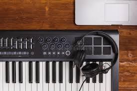 ion set midi piano keyboard retina laptop black dj headphones on wooden desk table