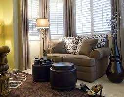 small sofa and floor lamp beside bay window