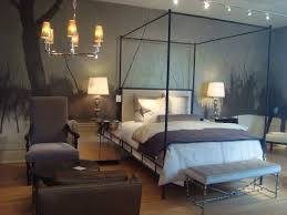 cozy bedroom with chandelier and four post bed with bedroom bench by oly studio
