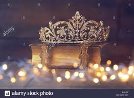 low key image of decorative crown on old book vine filtered with flitter overlay selective focus